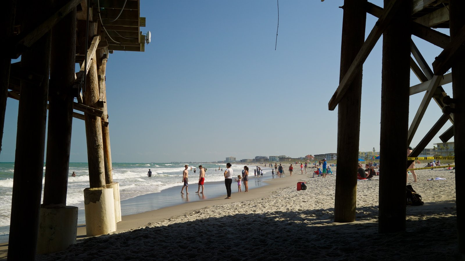 Cocoa Beach Pier showing a beach and general coastal views as well as a small group of people