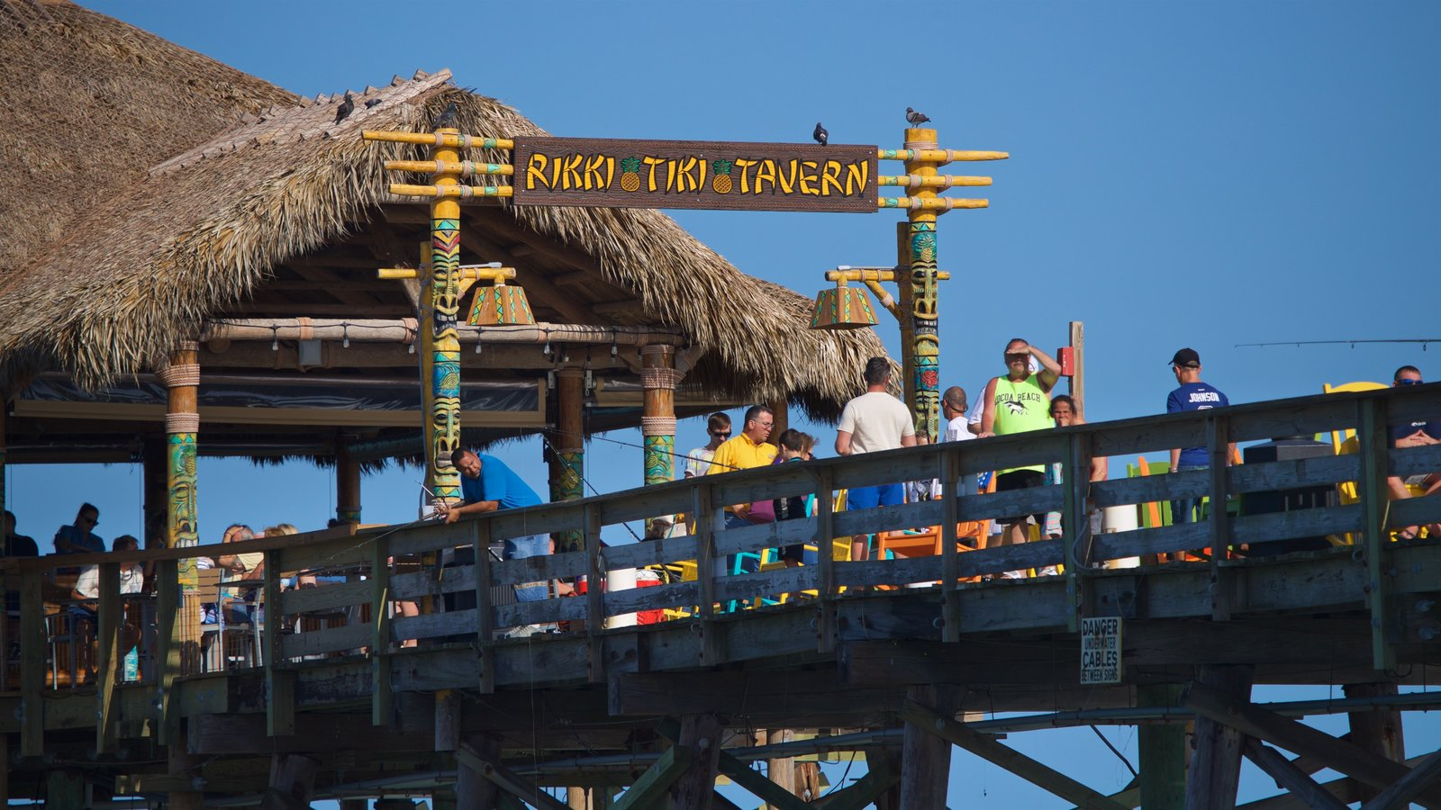 Cocoa Beach Pier featuring signage as well as a small group of people