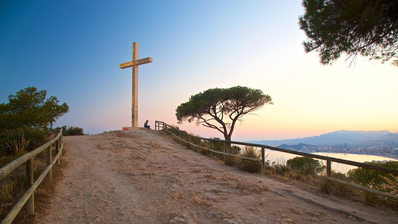La Cruz de Benidorm mostrando elementos religiosos, vistas de paisajes y una puesta de sol