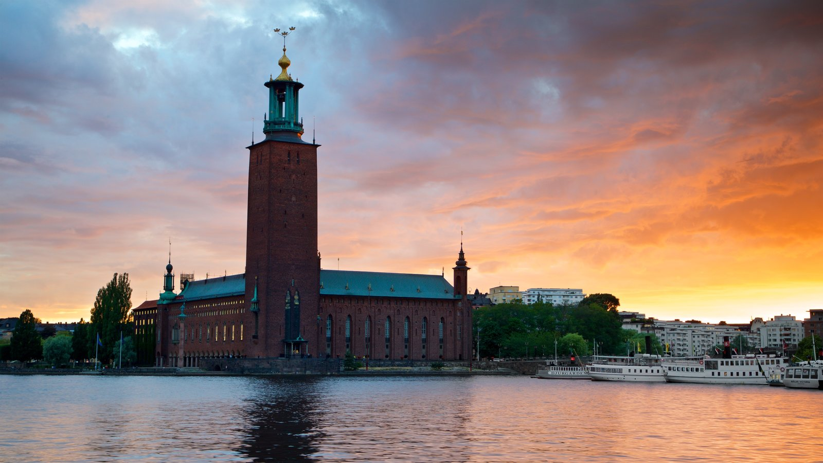 Stockholm City Hall which includes a bay or harbour, heritage architecture and a sunset