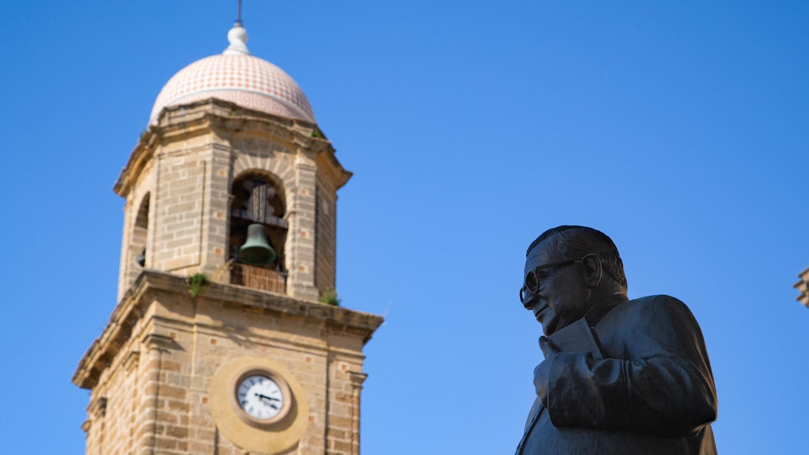Torre del reloj mostrando una estatua o escultura y elementos del patrimonio