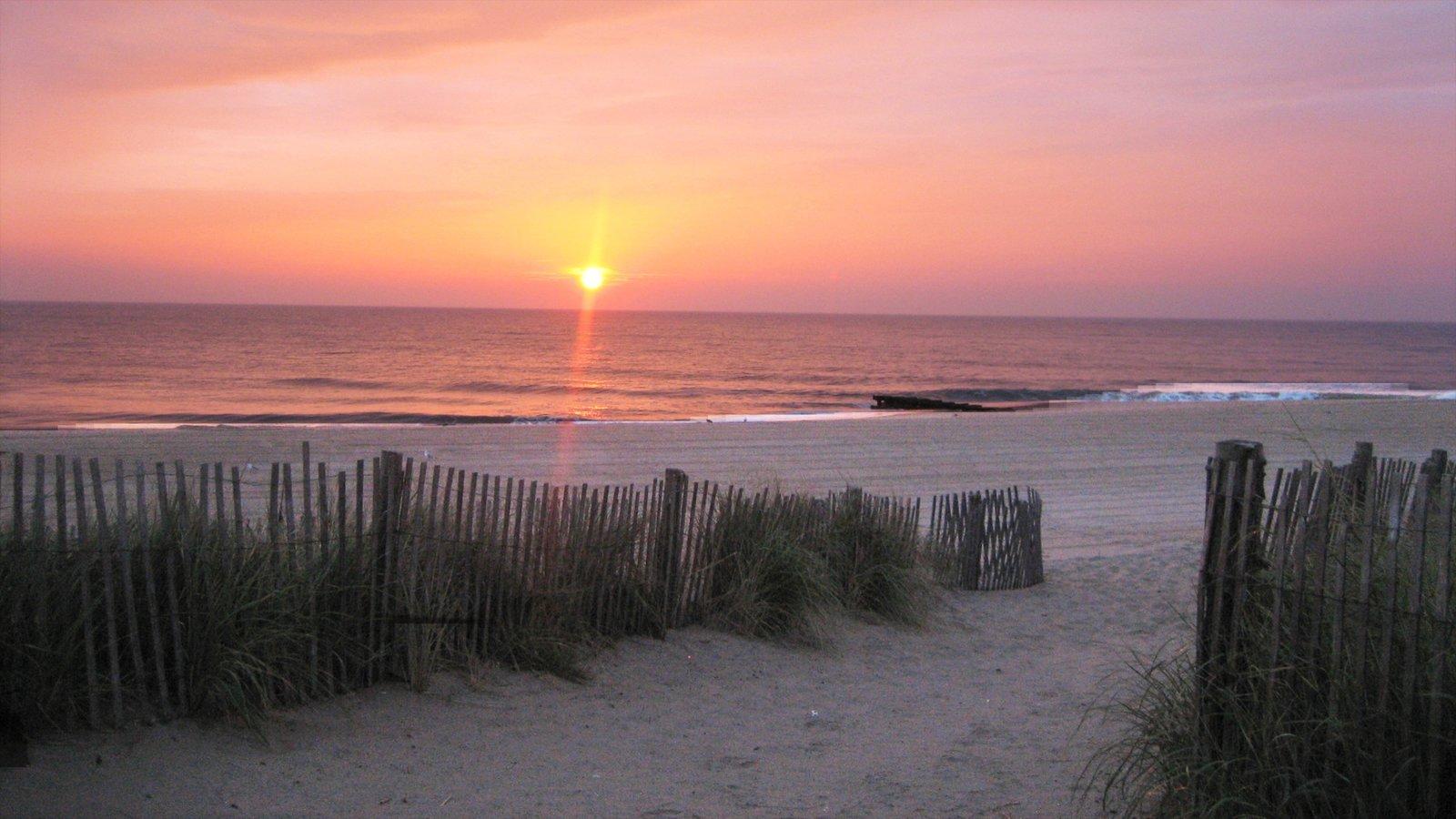 Rehoboth Beach ofreciendo una puesta de sol, una playa de arena y vistas generales de la costa