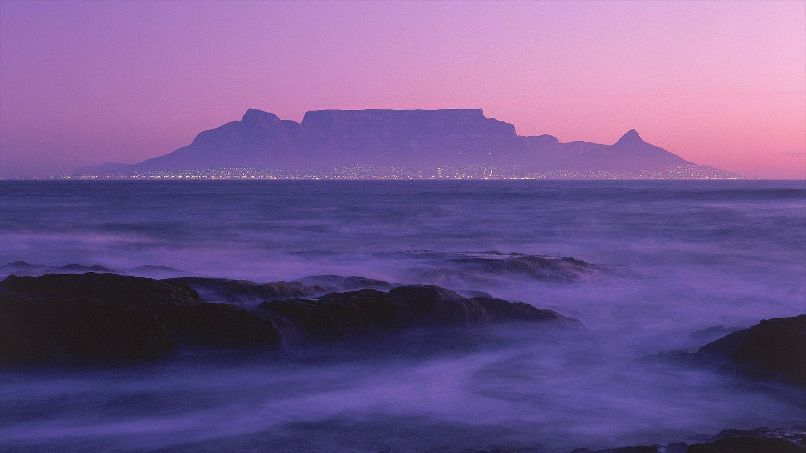 Cape Town showing mountains, a sunset and rocky coastline