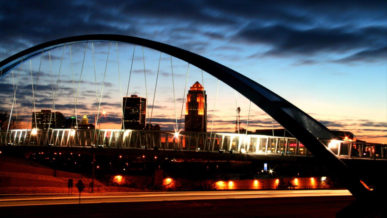 Des Moines caracterizando uma ponte suspensa ou passarela entre as árvores, linha do horizonte e um pôr do sol
