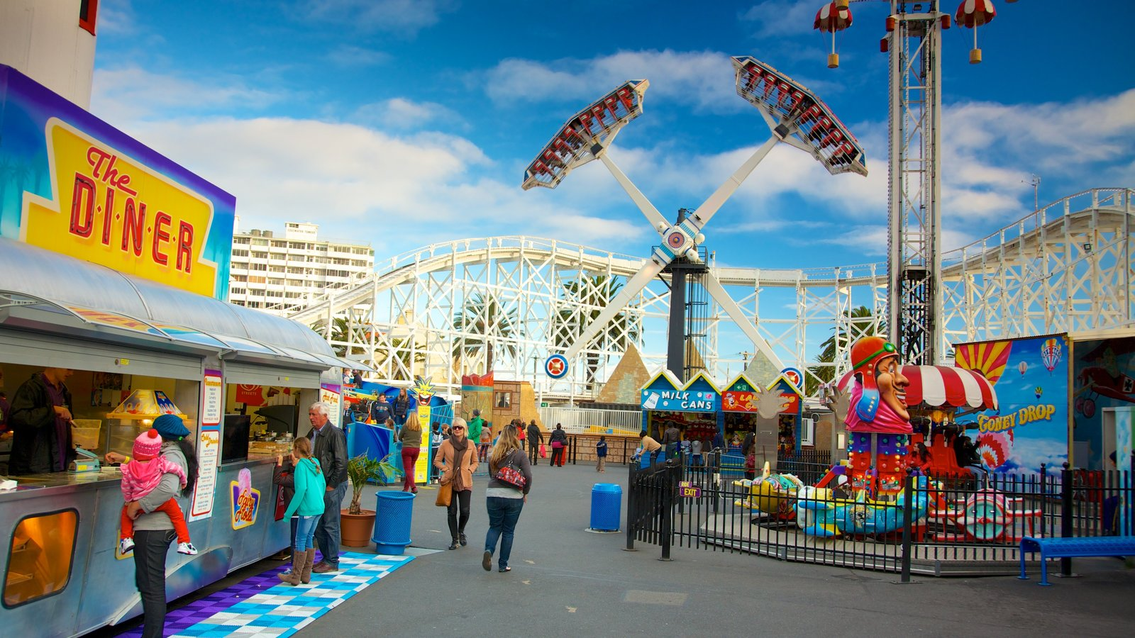 Luna Park showing rides and signage as well as a large group of people
