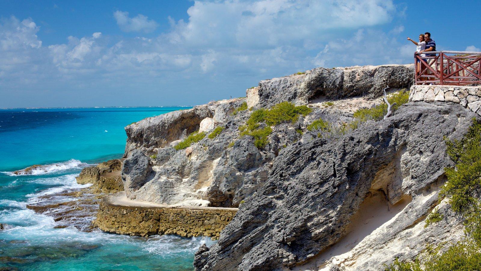 Isla Mujeres ofreciendo vistas y costa rocosa y también una pareja