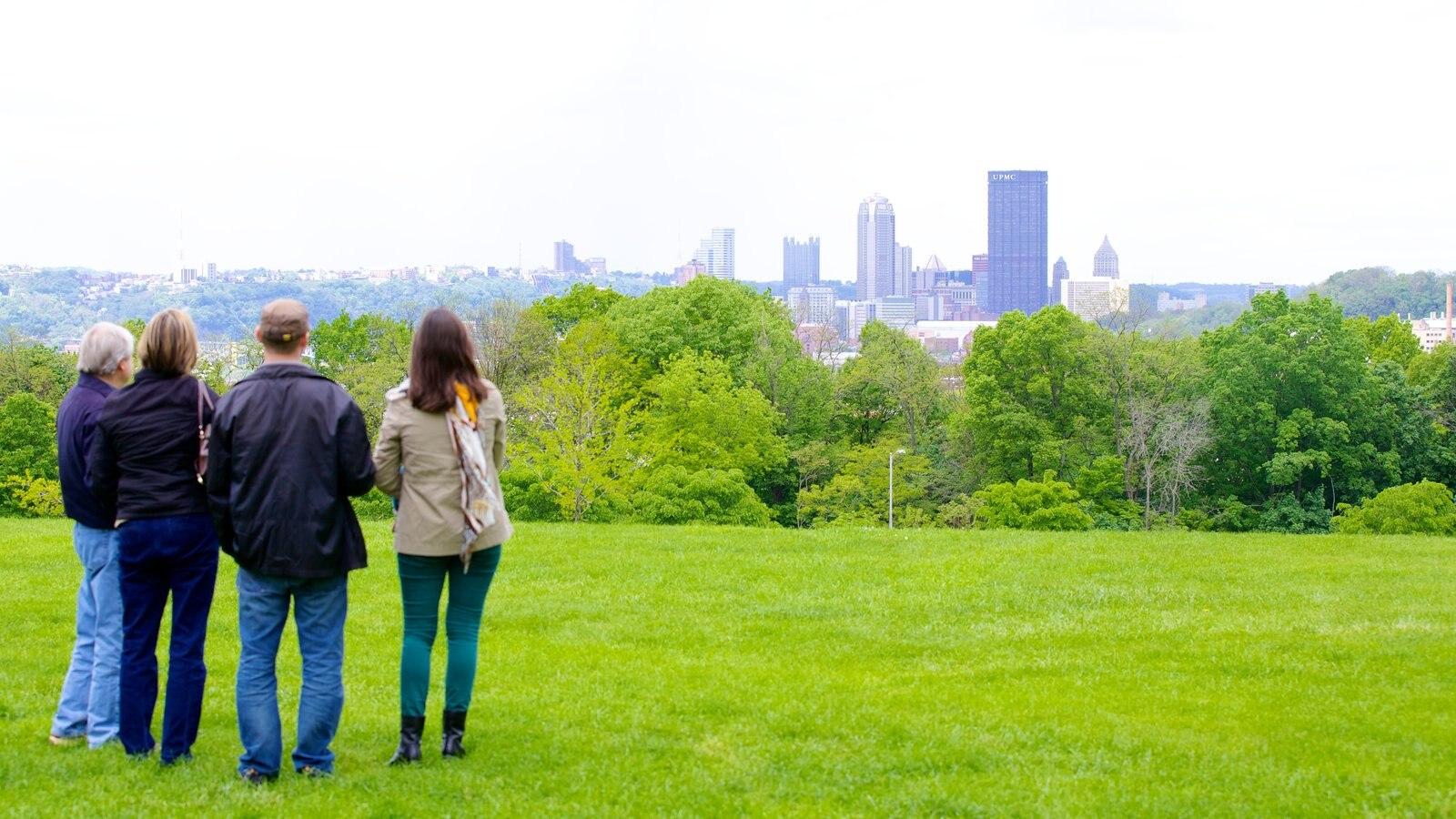 Pittsburgh caracterizando linha do horizonte e um jardim assim como um pequeno grupo de pessoas