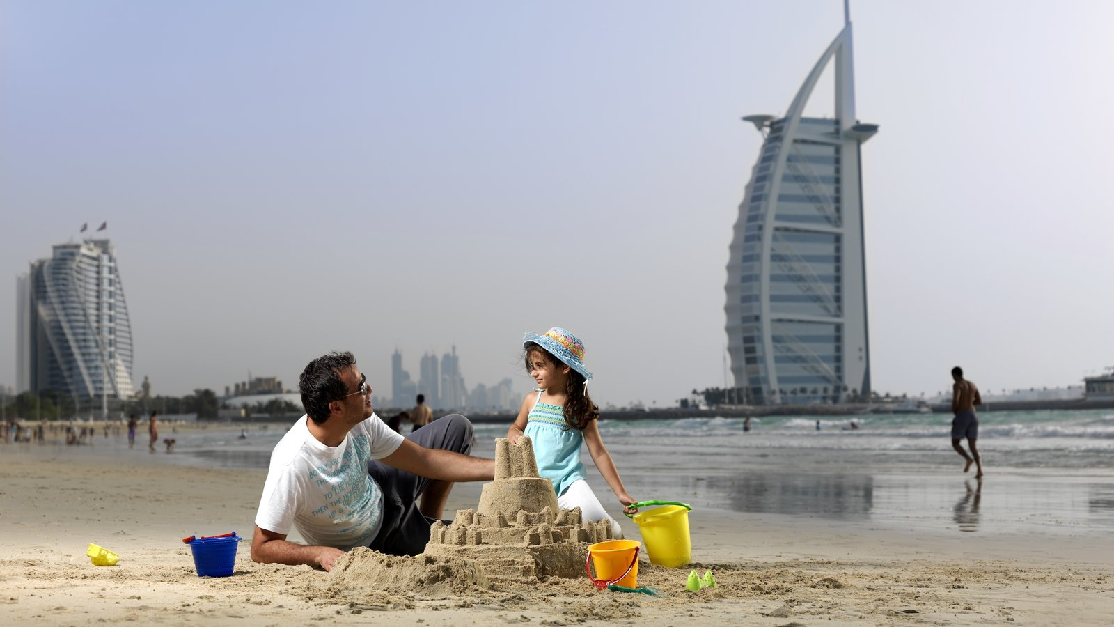 Jumeira Beach and Park showing a sandy beach as well as a small group of people
