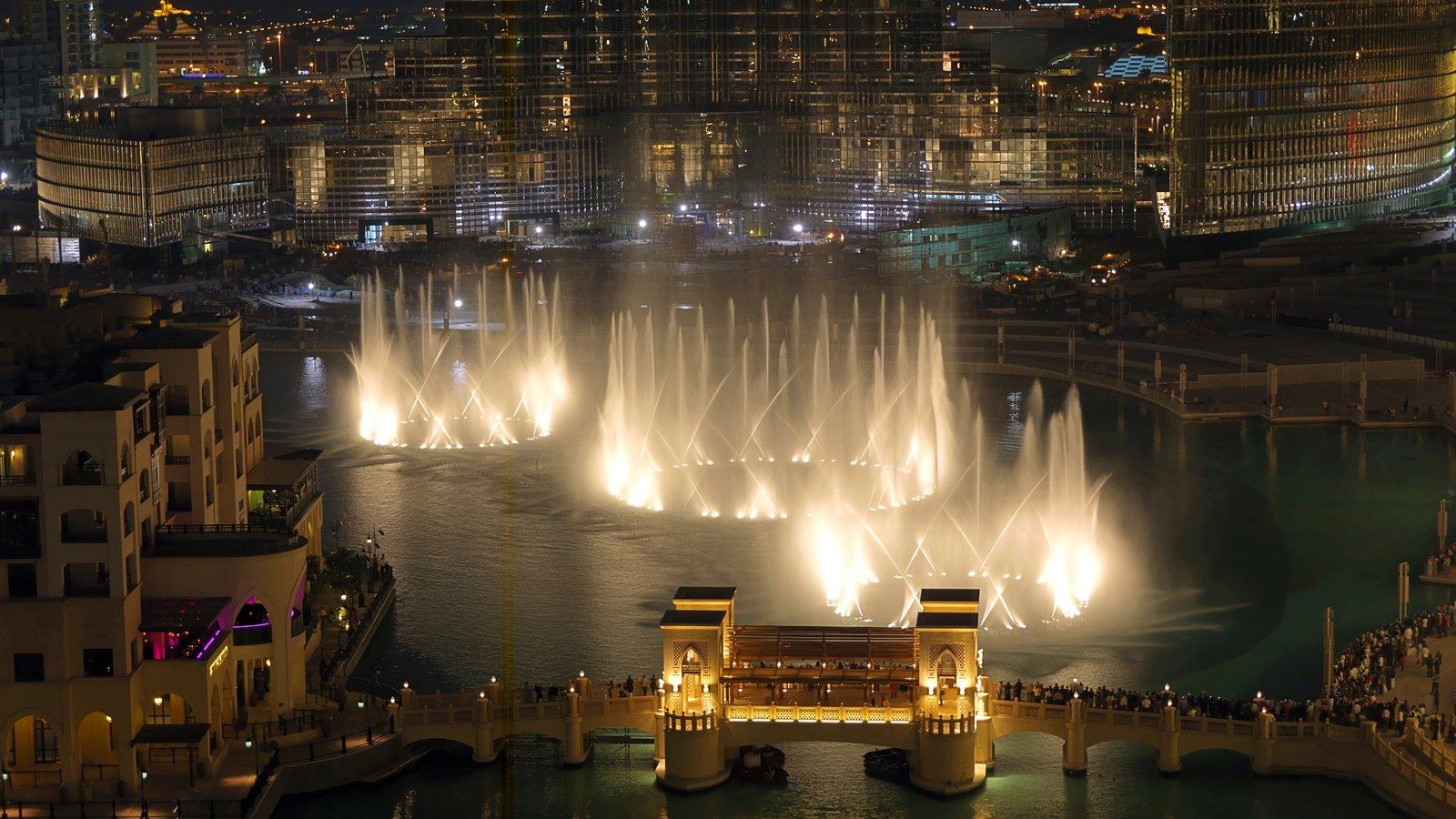 The Dubai Fountain featuring a fountain, night scenes and a city