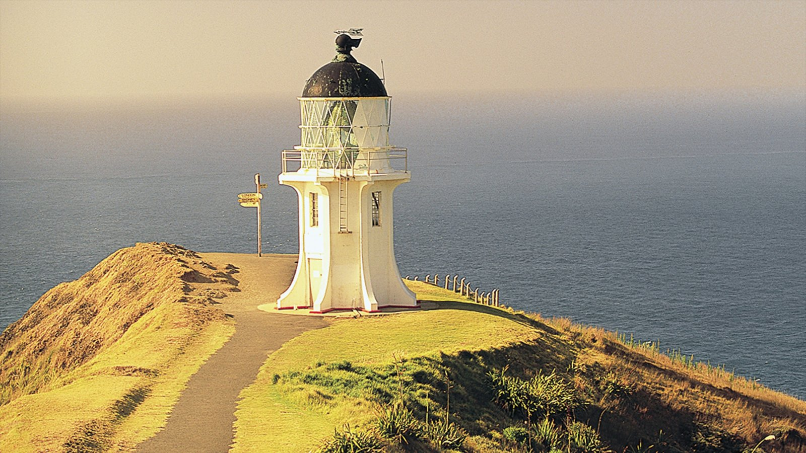 Cape Reinga Lighthouse que incluye vistas generales de la costa y un faro