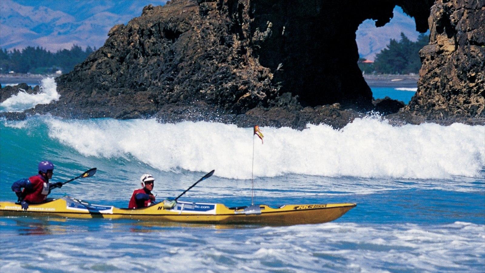 Dunedin showing surf, rocky coastline and kayaking or canoeing