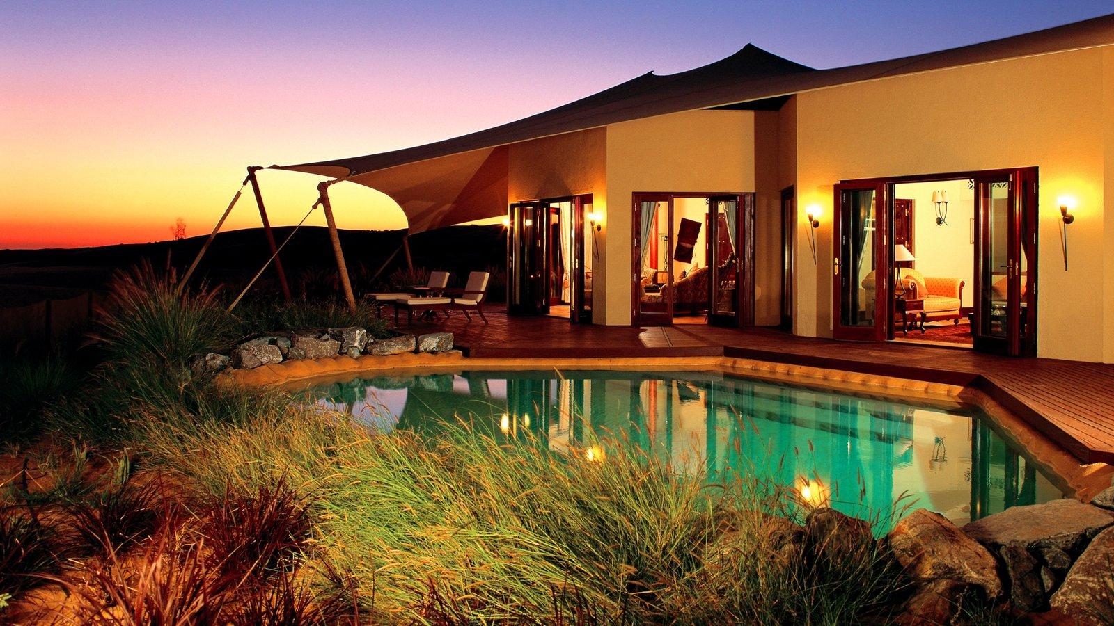 Dubai Desert featuring desert views, a sunset and a luxury hotel or resort