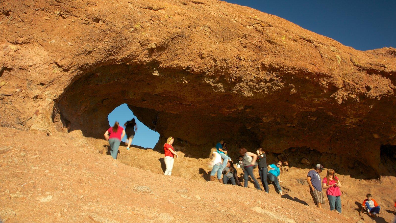 Hole in the Rock mostrando paisagens do deserto e escalada ou caminhada assim como um grande grupo de pessoas