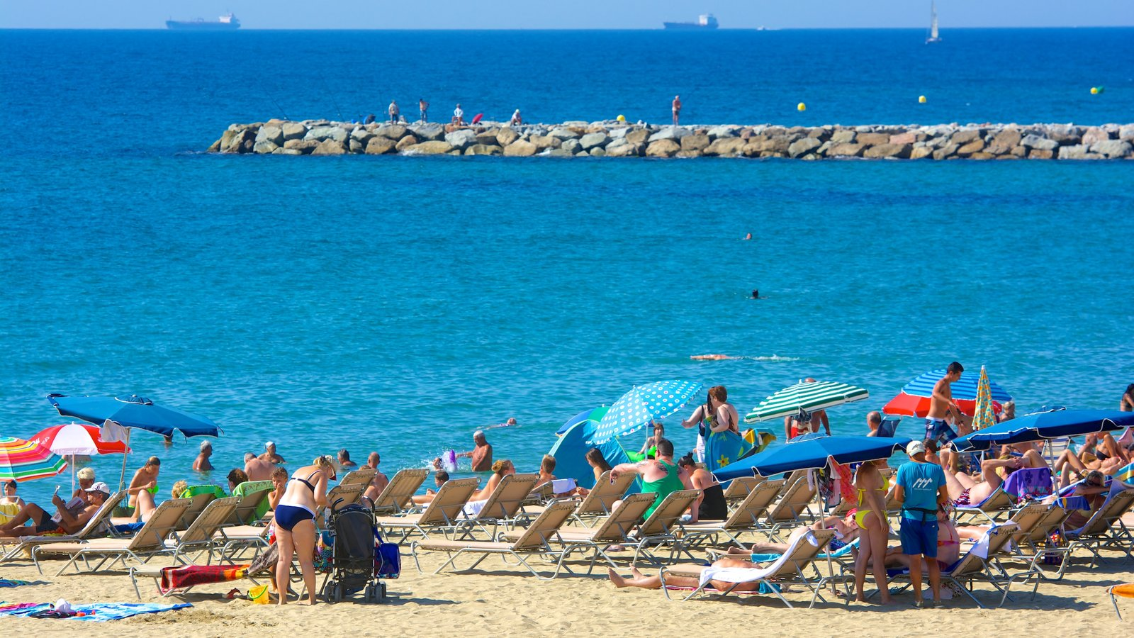 Barcelona featuring a sandy beach as well as a large group of people