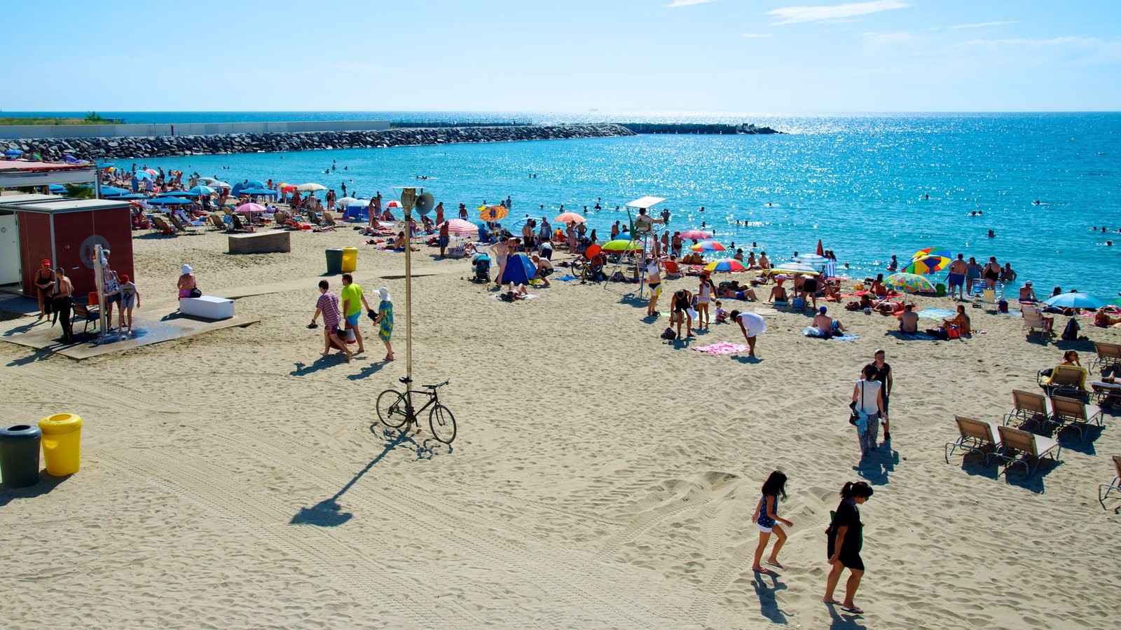 Llevant Beach which includes a sandy beach and general coastal views as well as a small group of people