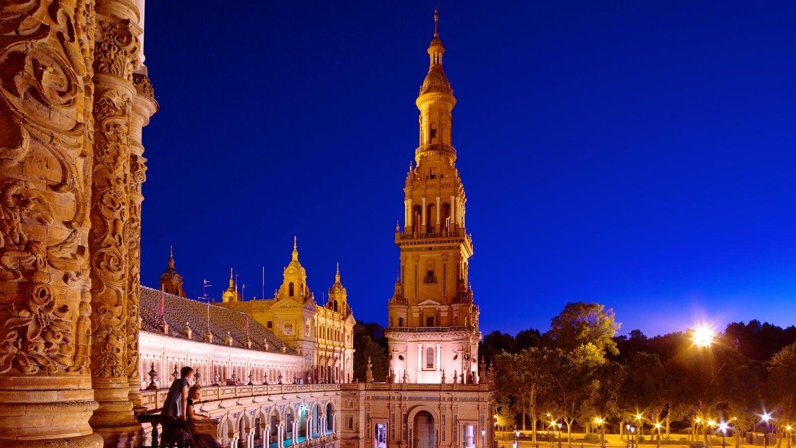 Plaza de España que inclui arquitetura de patrimônio, um pequeno castelo ou palácio e cenas noturnas