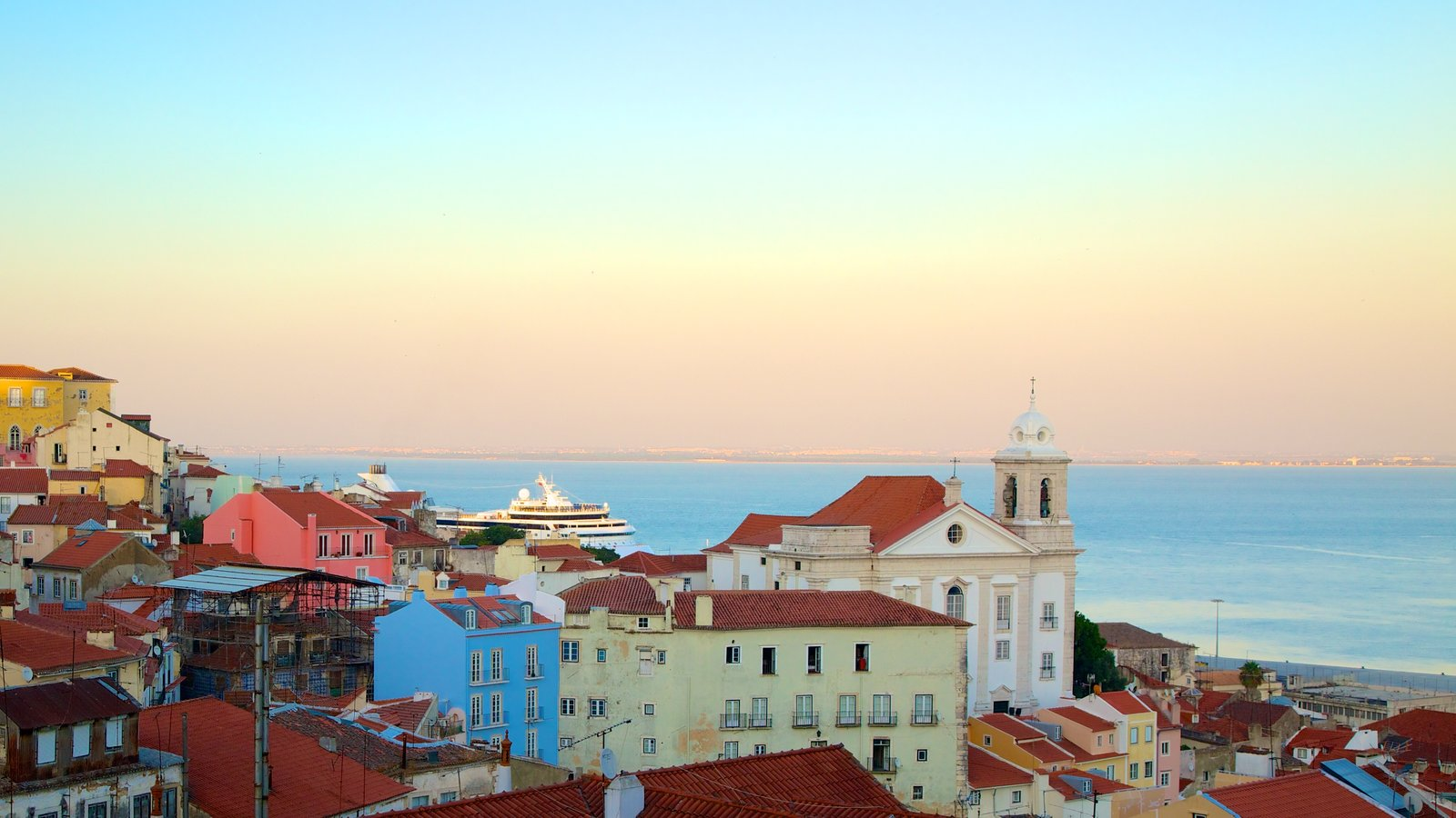 Alfama featuring a coastal town, a sunset and heritage architecture
