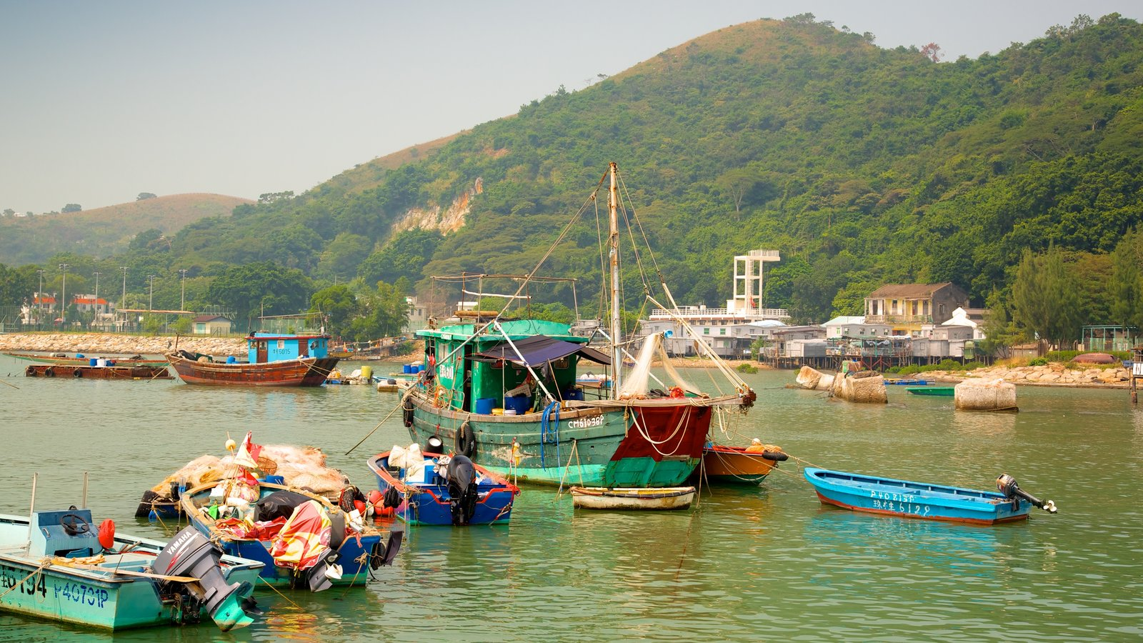 Tai O Fishing Village which includes a bay or harbor, mountains and boating
