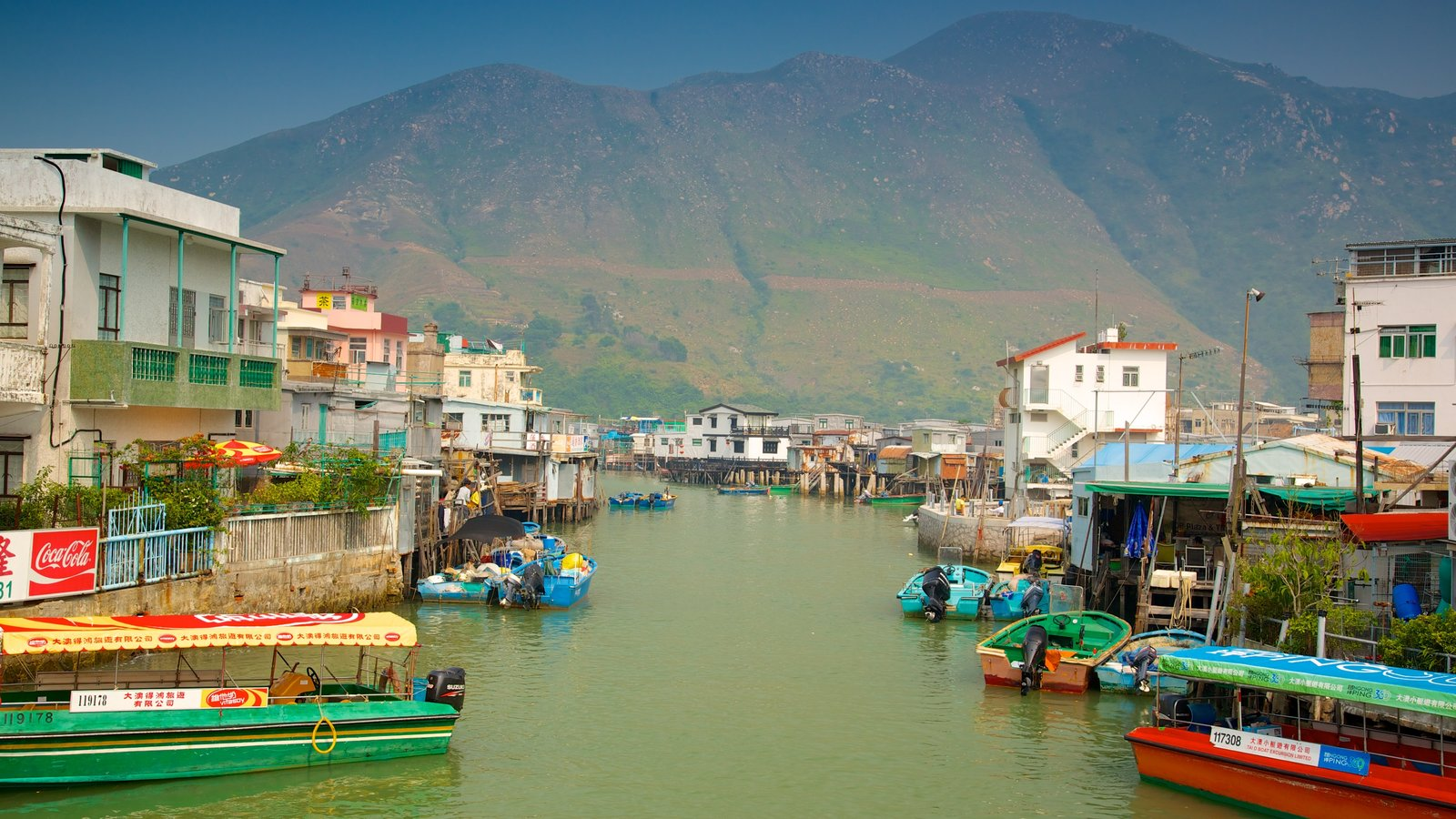 Tai O Fishing Village showing a river or creek, a small town or village and mountains