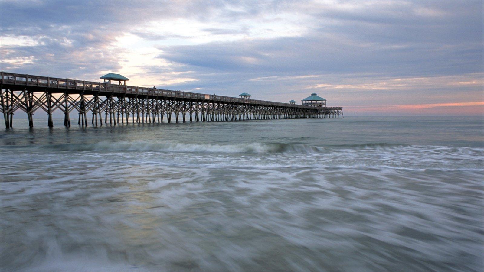 Folly Beach que inclui um pôr do sol, uma ponte e uma praia