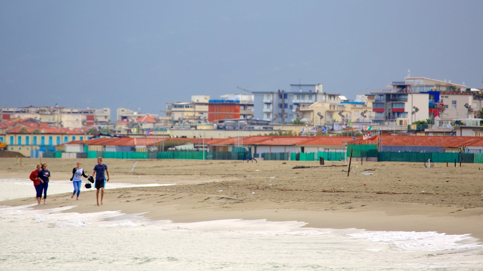 Viareggio featuring a coastal town and a sandy beach as well as a small group of people