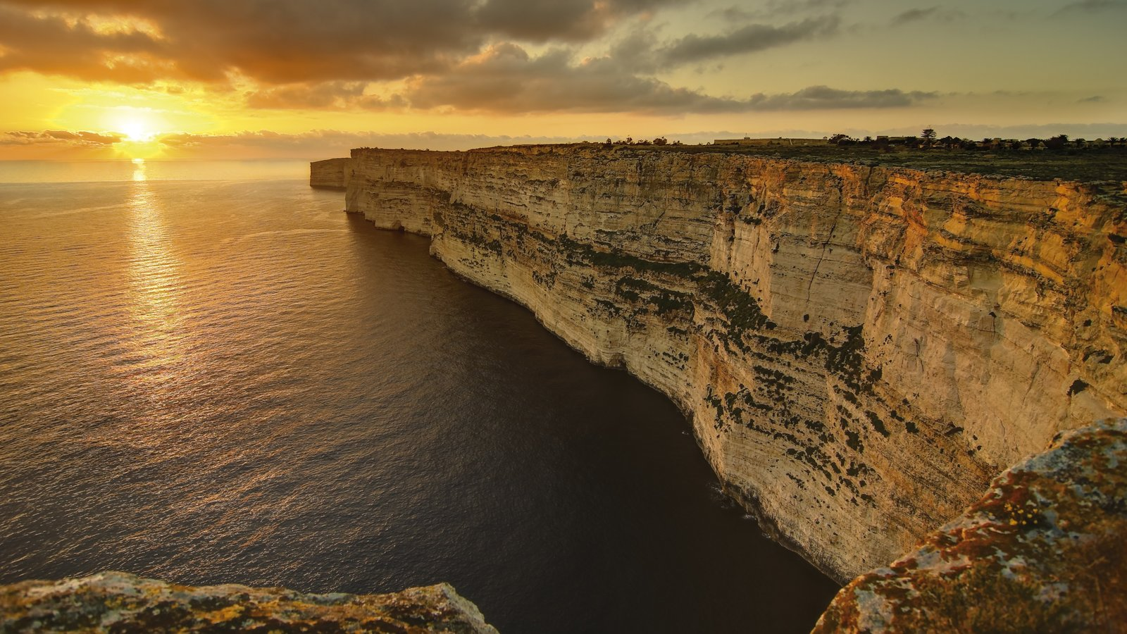 Gozo mostrando una puesta de sol, costa escarpada y vistas de paisajes