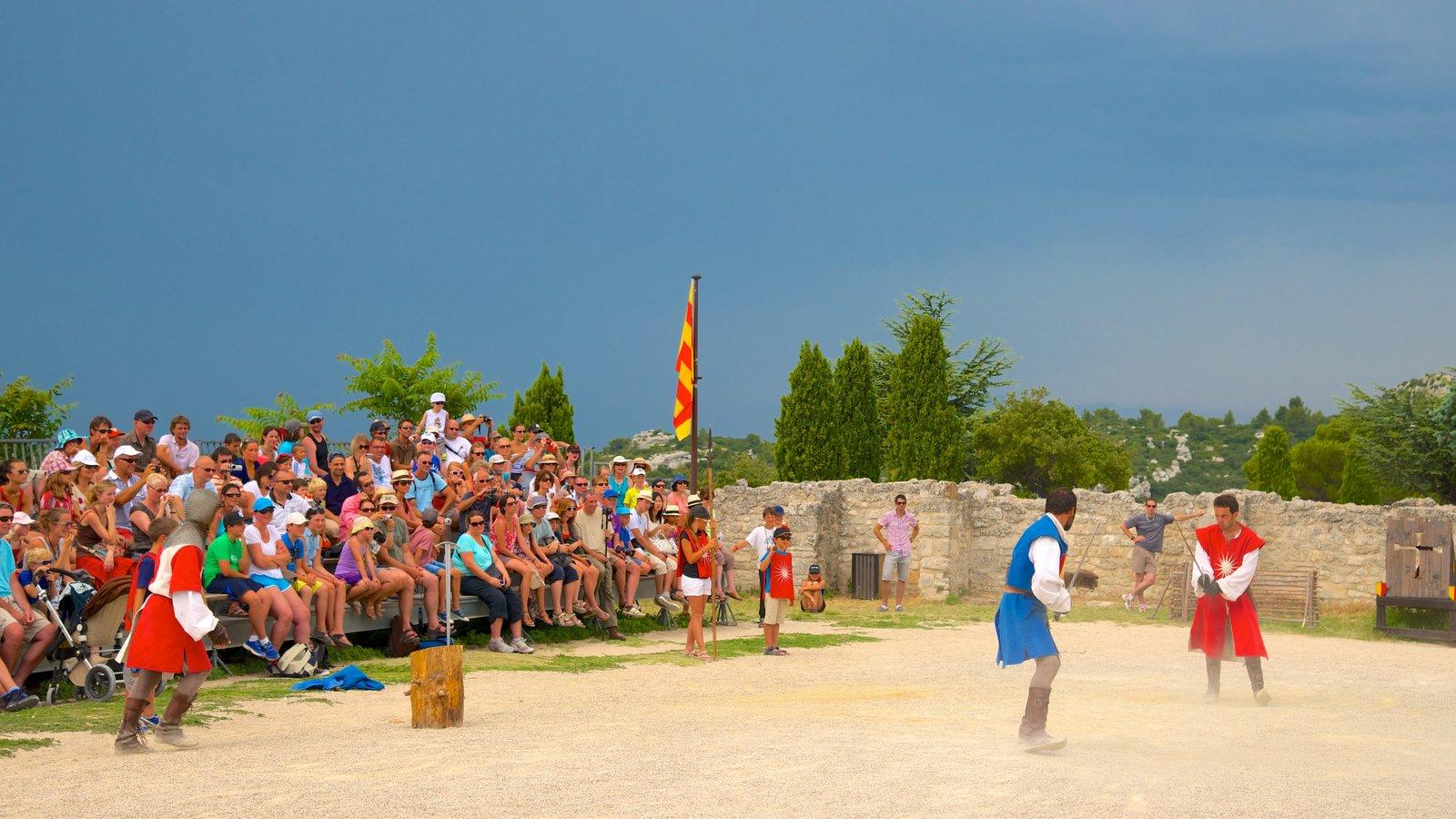 Chateau des Baux que inclui um castelo e arte performática assim como um grande grupo de pessoas