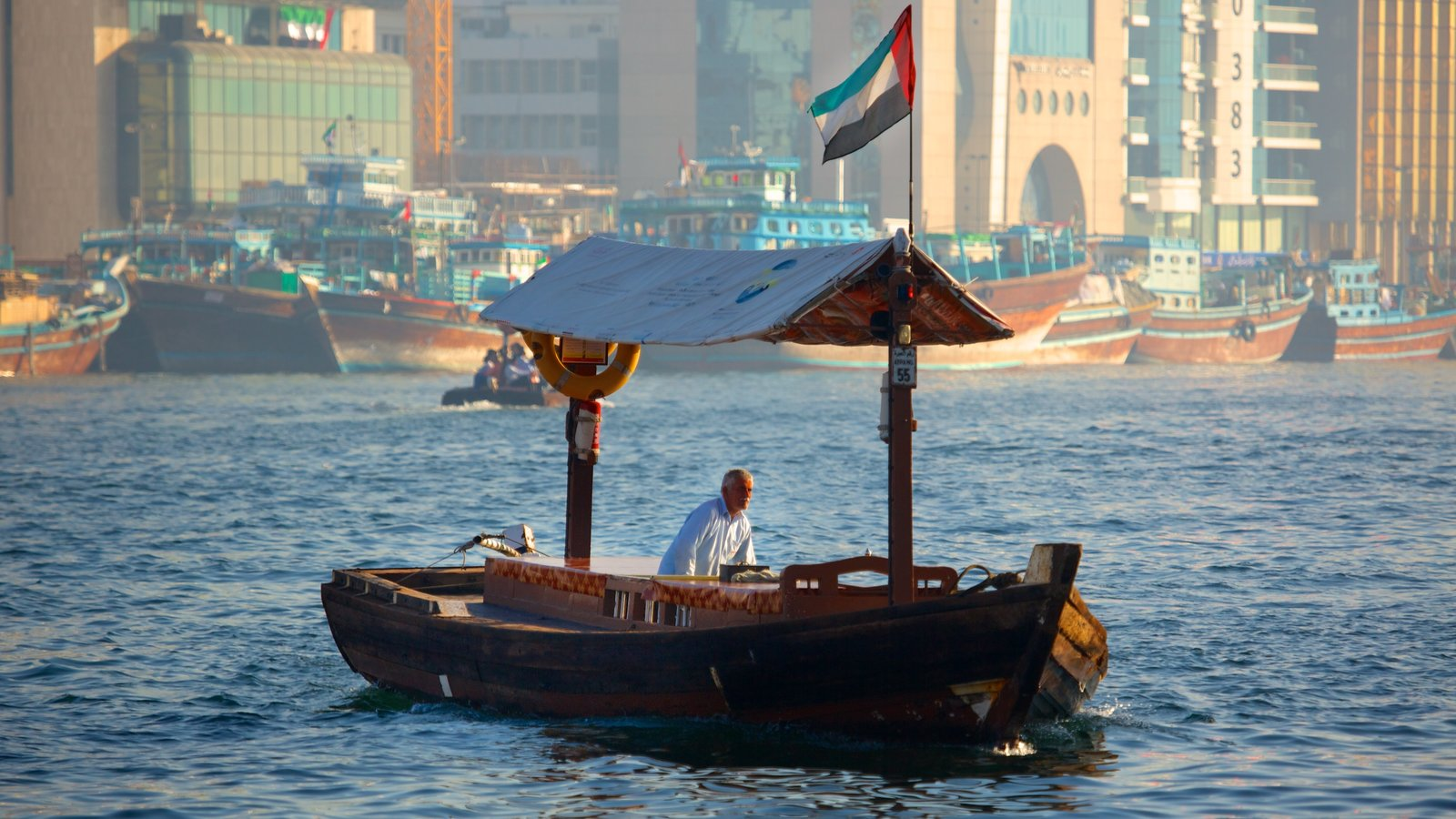 Dubai Creek featuring boating and a river or creek as well as an individual male