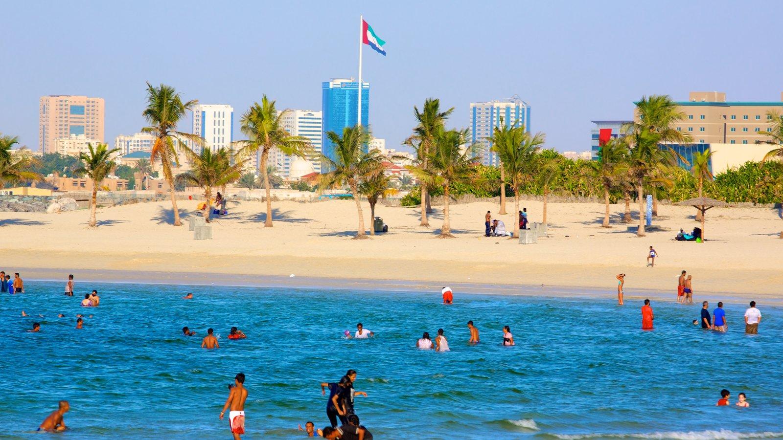 Al Mamzar Beach Park featuring a beach, swimming and tropical scenes