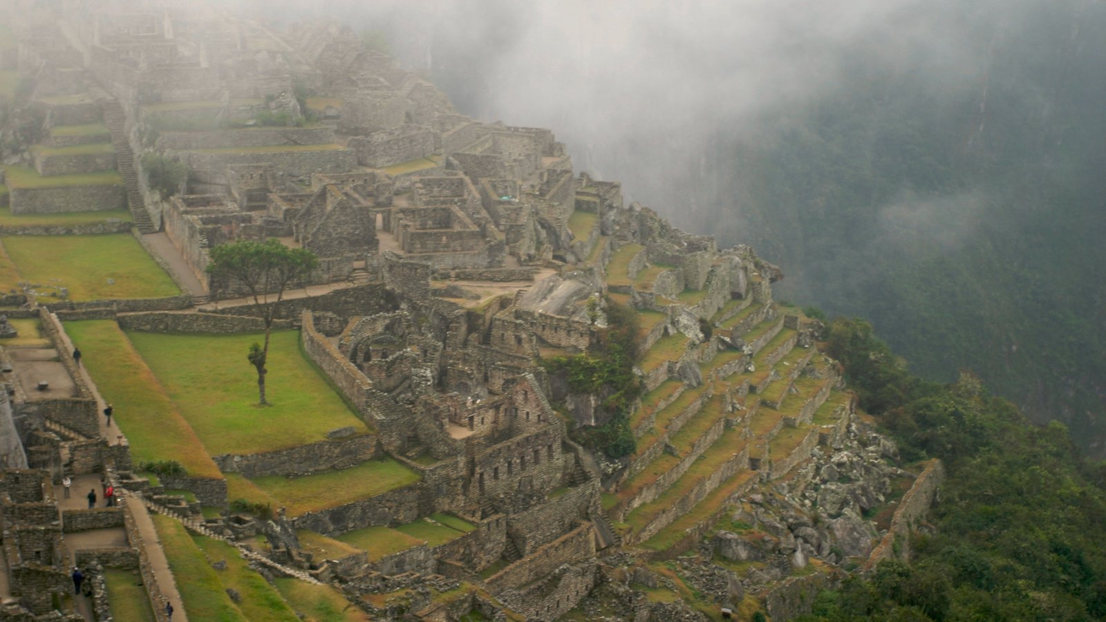 Machu Picchu showing mountains, a ruin and mist or fog