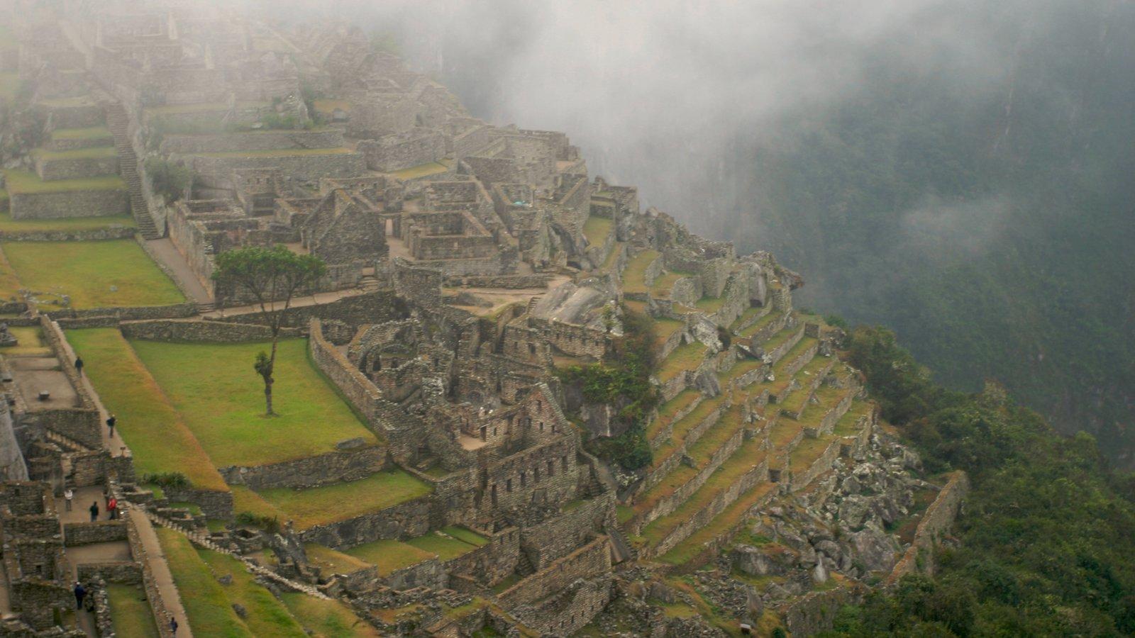 Machu Picchu caracterizando montanhas, neblina e uma ruína