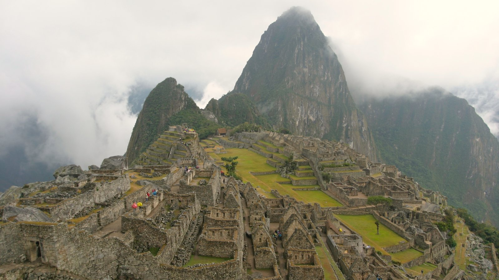 Machu Picchu showing building ruins, mist or fog and mountains