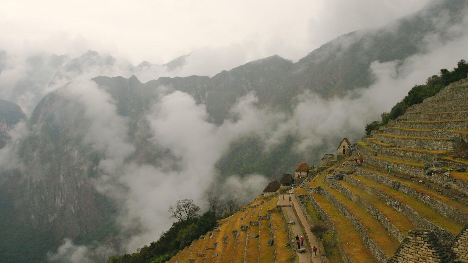 Machu Picchu mostrando neblina, uma ruína e montanhas