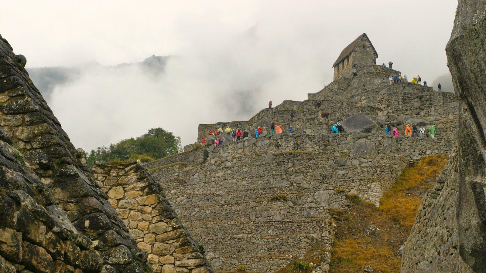 Machu Picchu mostrando escalada ou caminhada, neblina e uma ruína