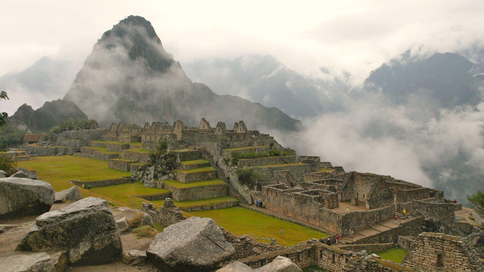 Machu Picchu caracterizando montanhas, ruínas de edifício e neblina