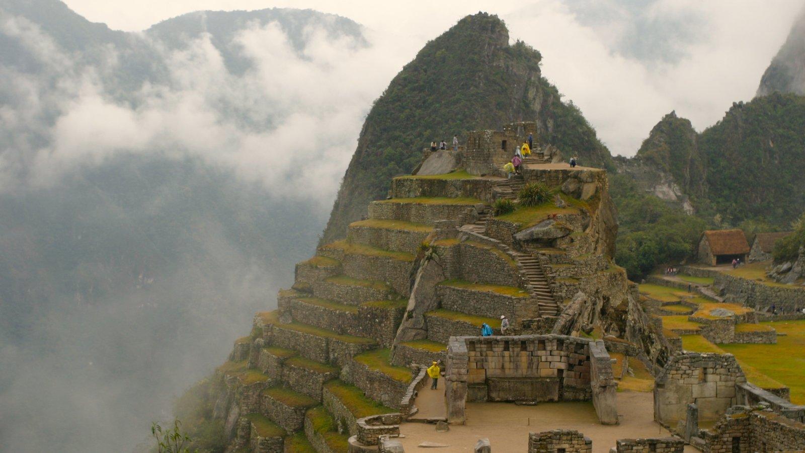 Machu Picchu mostrando neblina, montanhas e ruínas de edifício