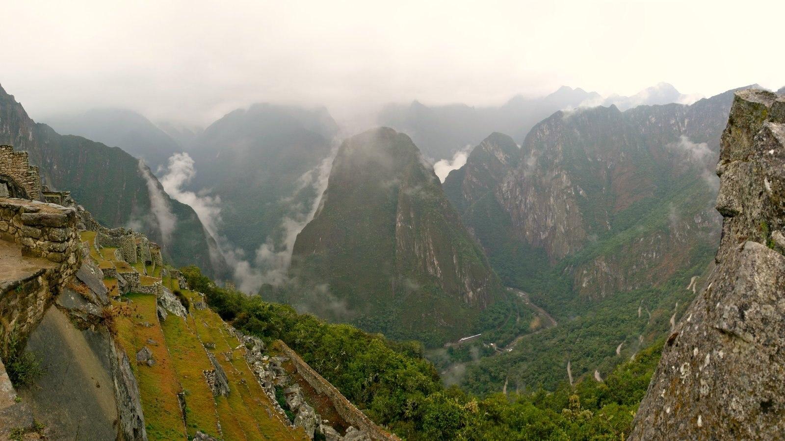 Machu Picchu mostrando ruínas de edifício, neblina e montanhas