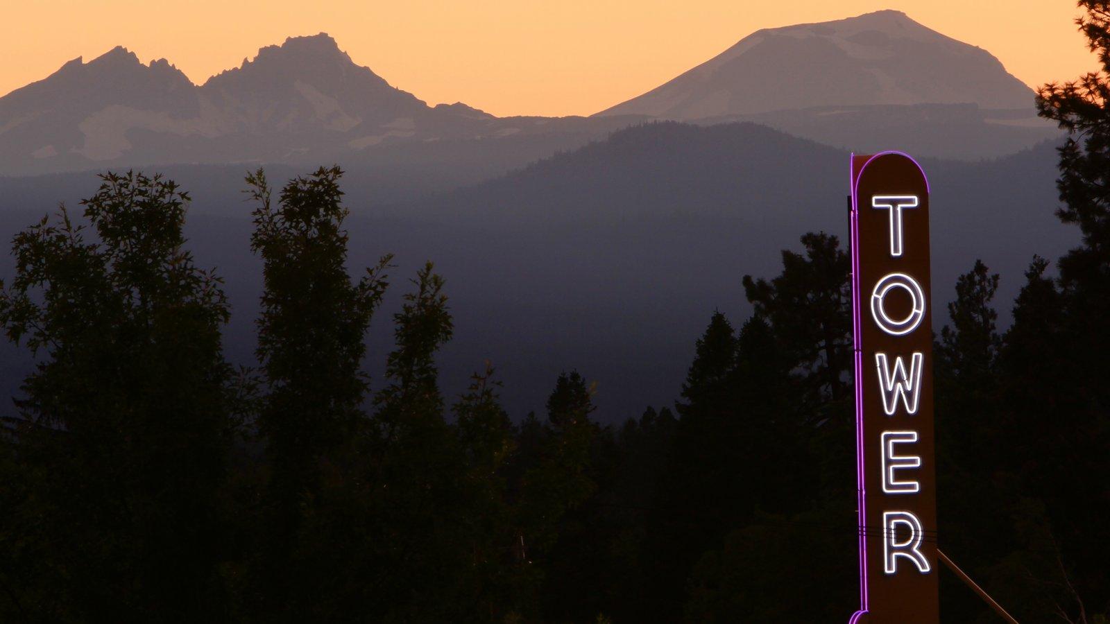 Bend mostrando señalización, montañas y una puesta de sol