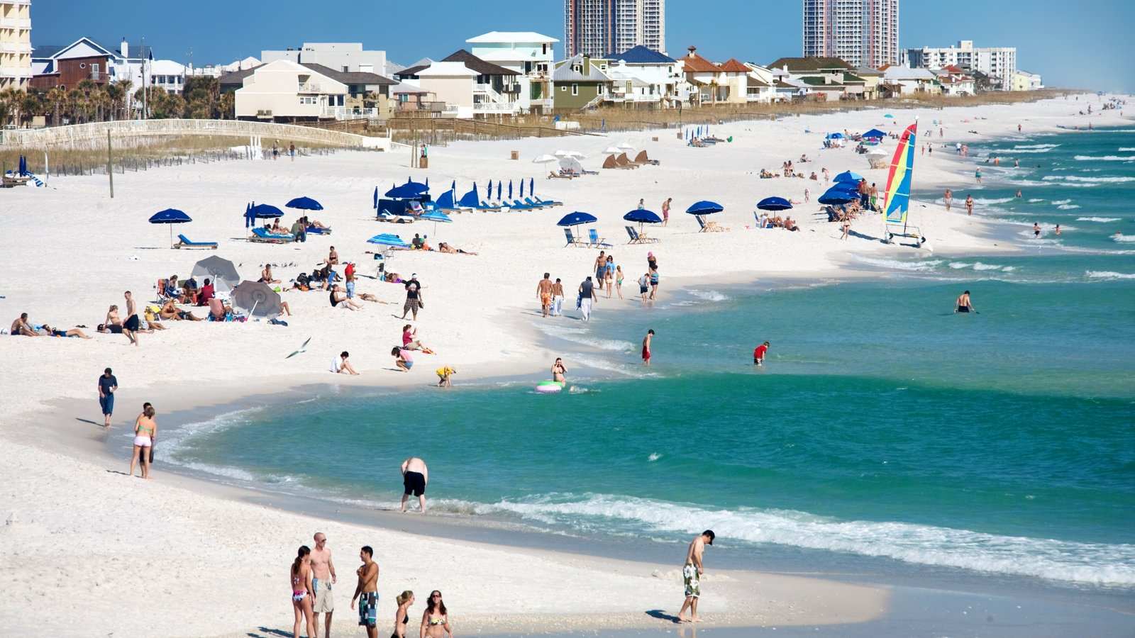 Pensacola showing a sandy beach and a coastal town as well as a large group of people