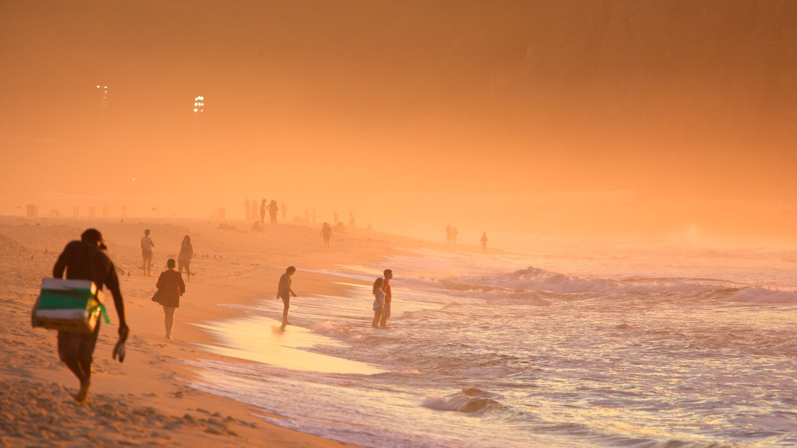 Copacabana Beach featuring a sandy beach, mist or fog and a sunset