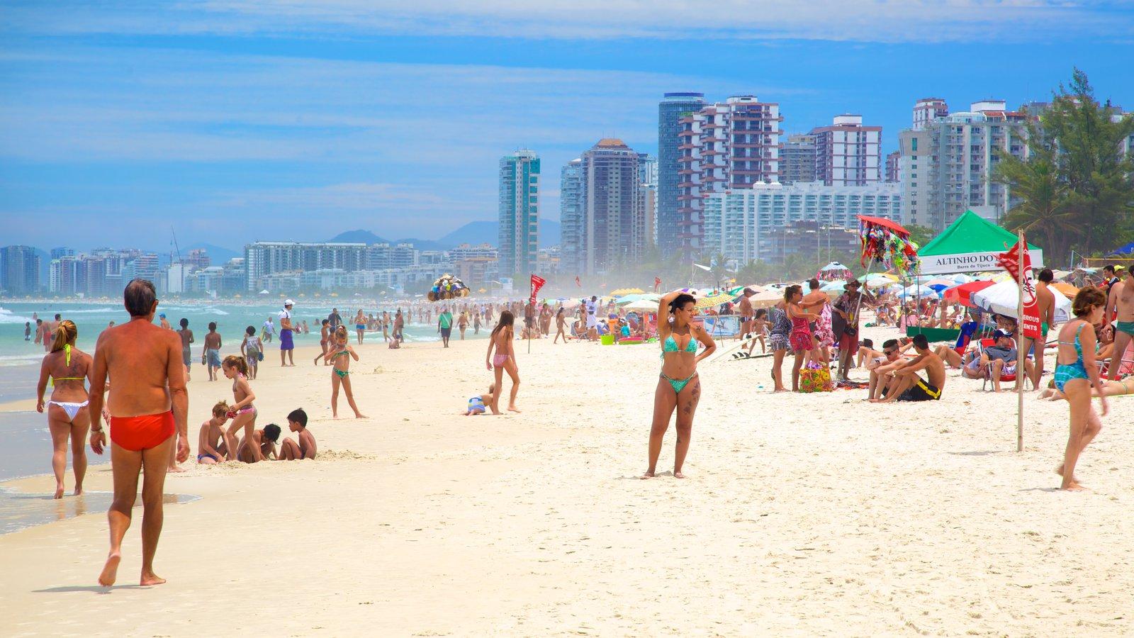 Barra da Tijuca caracterizando uma praia de areia assim como um grande grupo de pessoas
