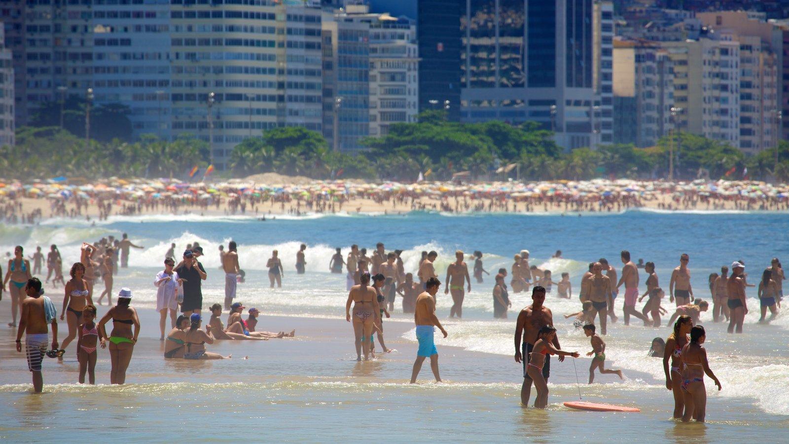 Praia de Copacabana que inclui uma praia de areia e natação assim como um grande grupo de pessoas
