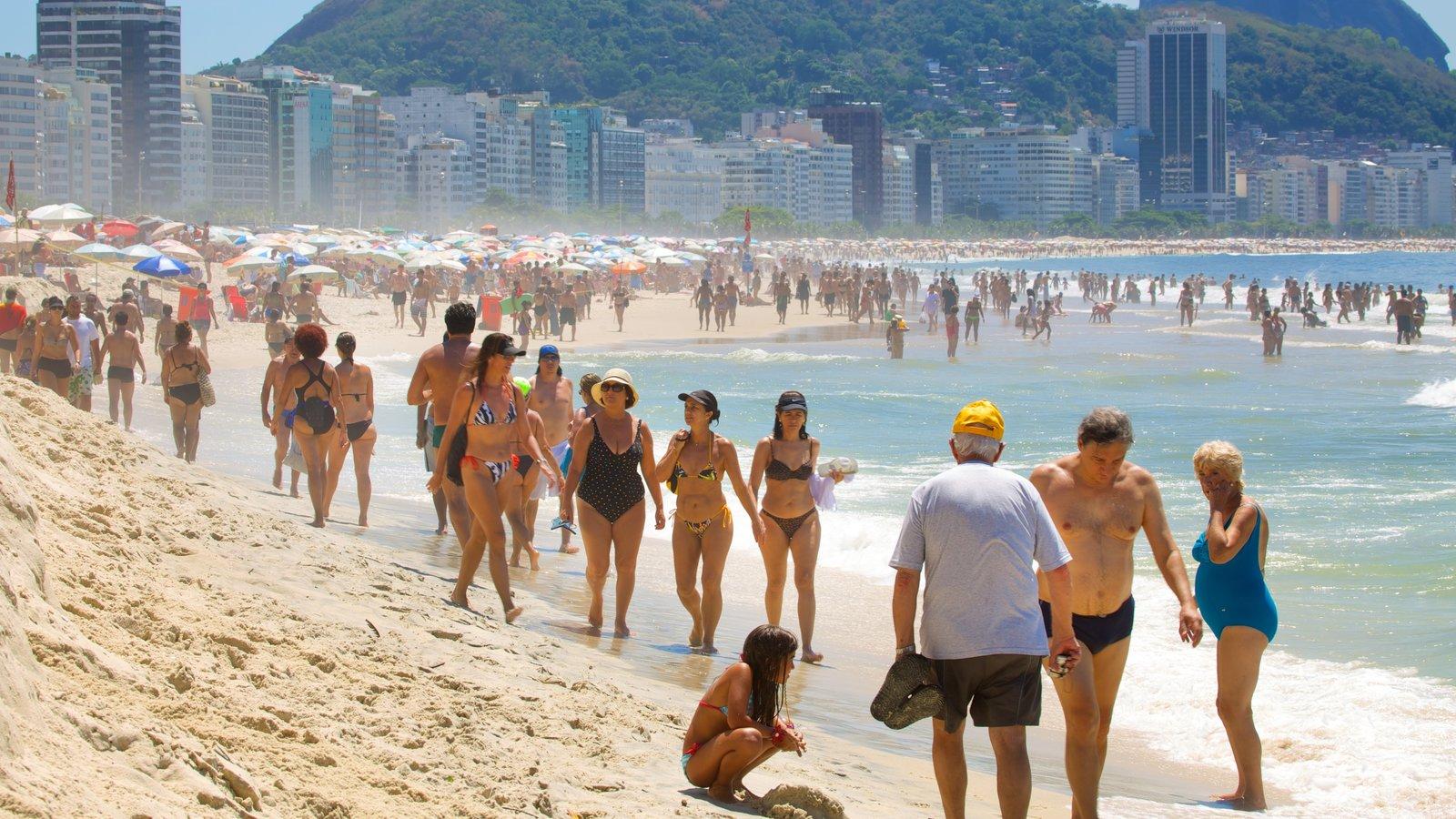 Praia de Copacabana que inclui natação e uma praia assim como um grande grupo de pessoas