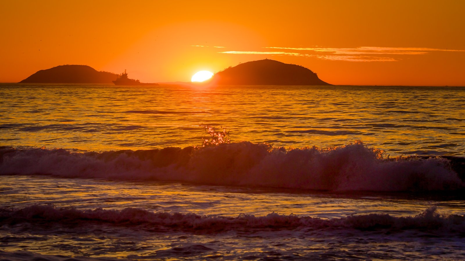 Copacabana Beach showing surf and a sunset