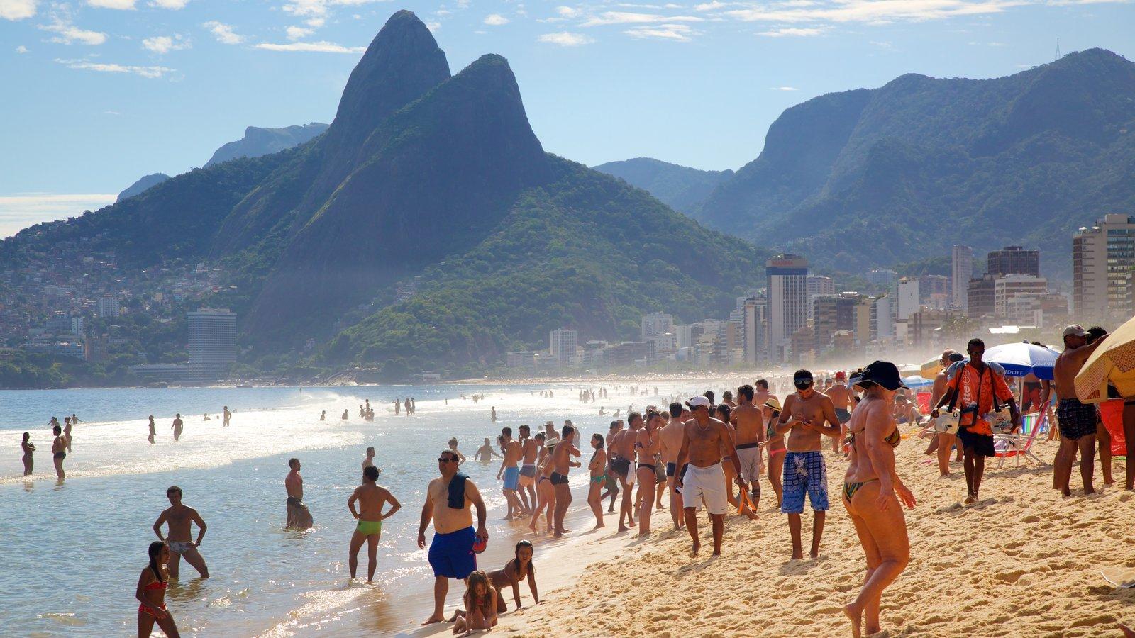 Praia de Ipanema que inclui uma praia de areia e montanhas assim como um grande grupo de pessoas