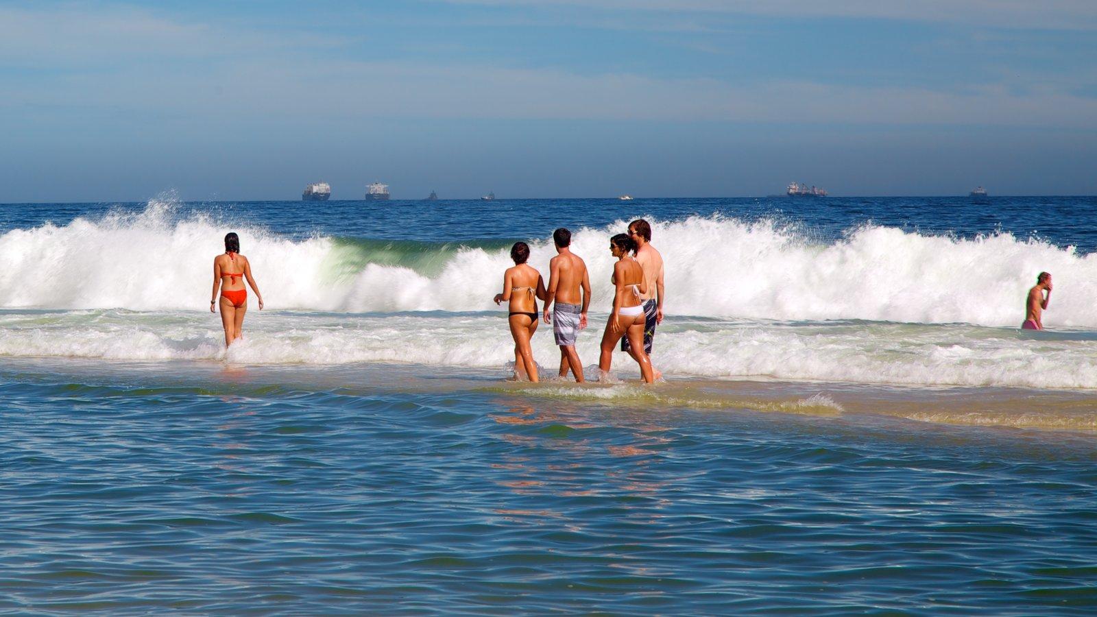 Praia de Ipanema caracterizando surfe e natação assim como um pequeno grupo de pessoas
