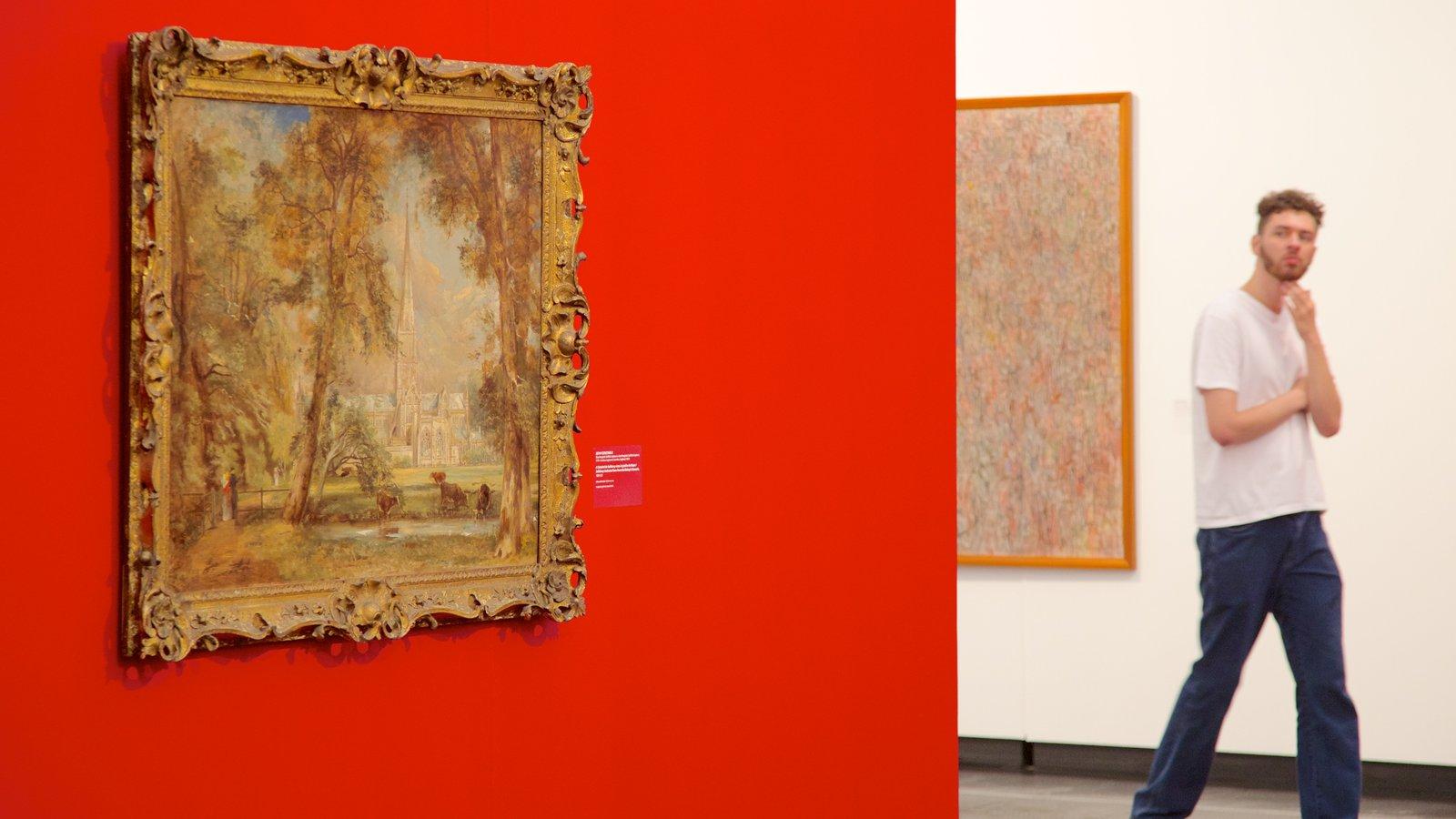 Museu de Arte Moderna mostrando arte e vistas internas assim como um homem sozinho