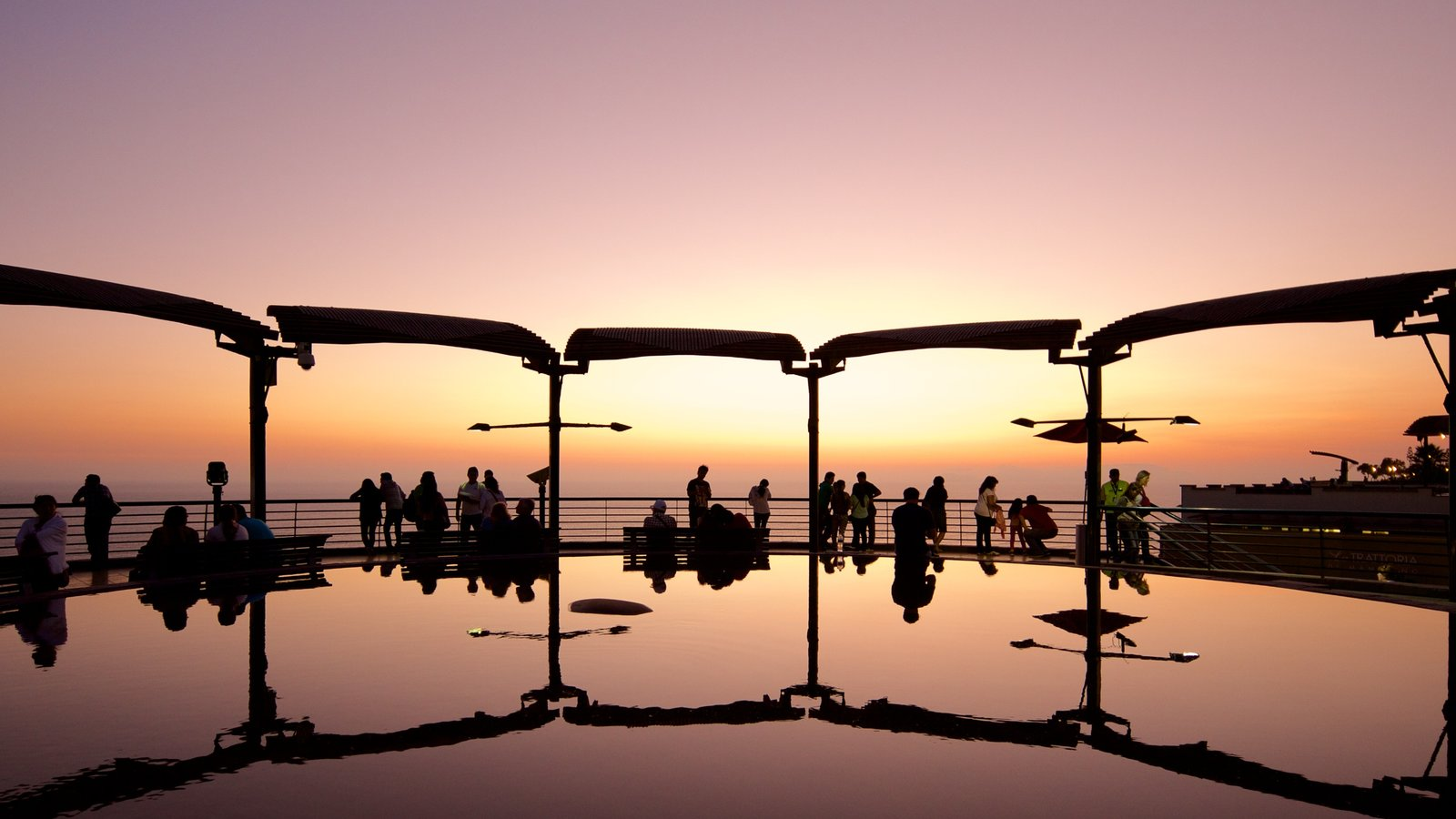 Lima featuring a sunset and a pond as well as a large group of people