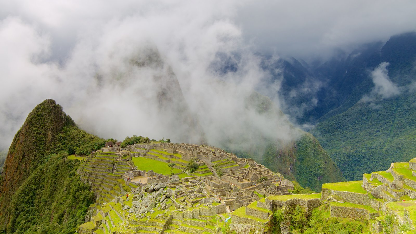 Machu Picchu showing mountains, mist or fog and building ruins