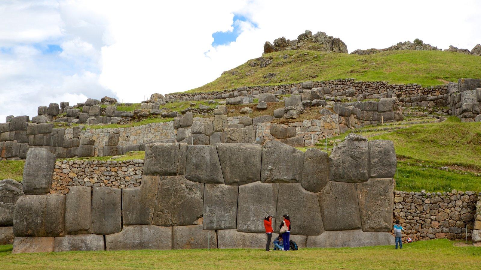 Sacsayhuaman caracterizando uma ruína e elementos de patrimônio assim como um pequeno grupo de pessoas